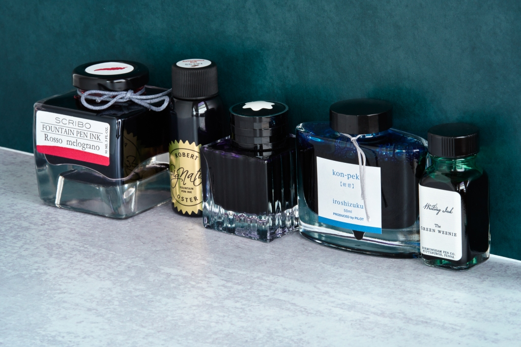 A collection of fountain pen inks. From left to right: Scribo Rosso Melograno, Robert Oster Astorquiza Rot, Montblanc Psychedelic Purple, Iroshizuku Kon-Peki, Birmingham Green Weenie.