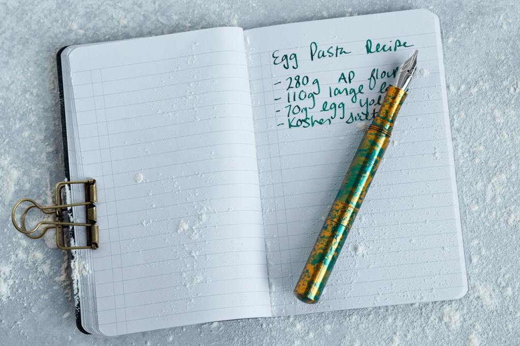 Schon Pocket Six Fountain pen in Amphibian 3 sitting on top of a flour covered notebook with a recipe for fresh pasta written in it.