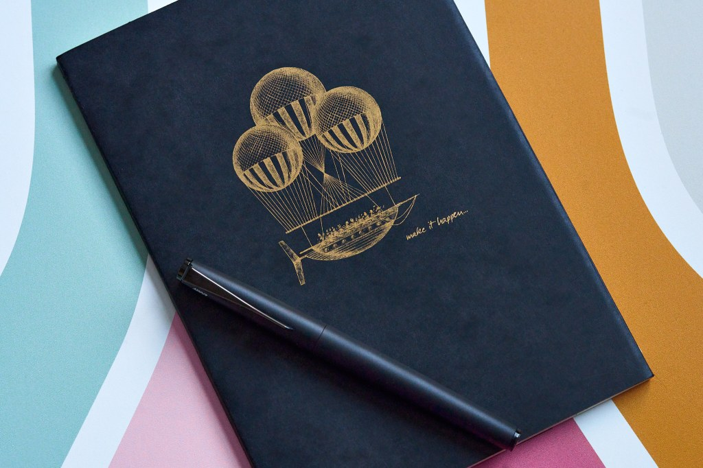 A Clairefontaine black Flying Spirit notebook sitting closed on desk with a Lamy Studio pen lying across it. The cover of the book features golden steampunk inspired airship