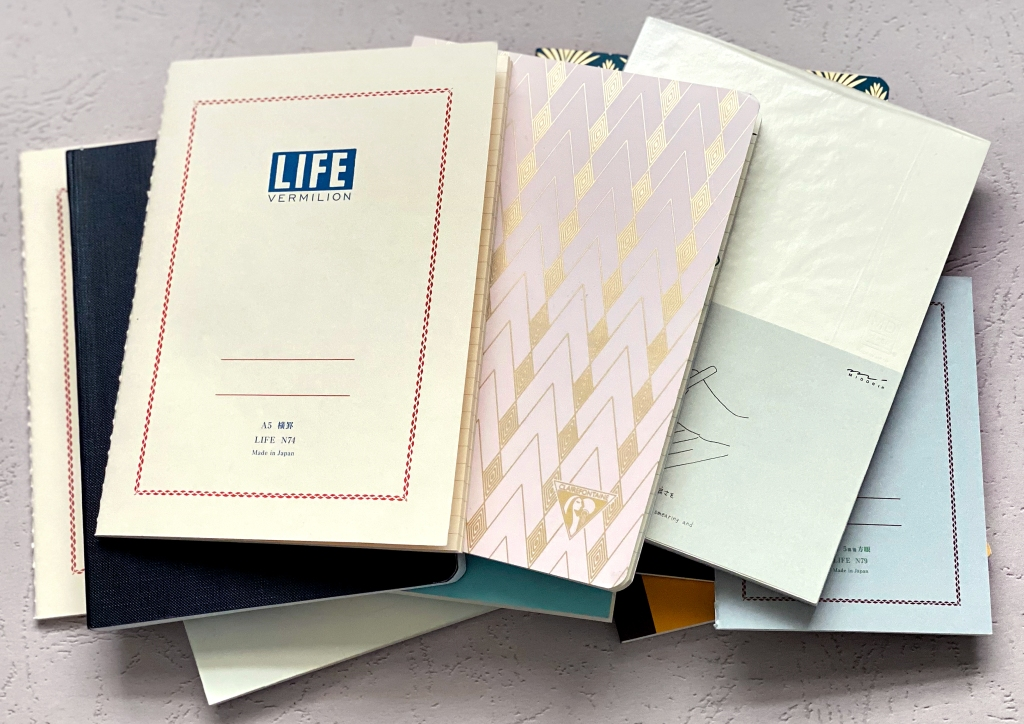 A pile of assorted notebooks featured in this article, including options from Clairfontaine, Life, Midori, Galen Leather, and more.